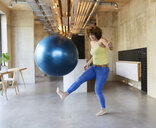 Woman shooting a fitness ball in modern office - FMKF05659