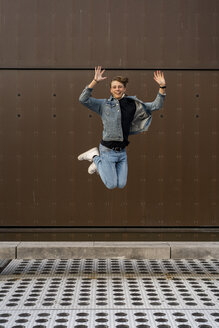 Young man jumping in front of a wall - AFVF02775