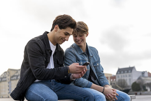 Denmark, Copenhagen, two young men sitting on a bench using cell phone - AFVF02784