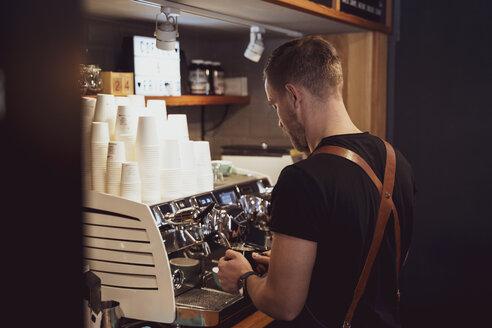 Rear view of barista preparing a coffee in coffee shop - OCMF00418