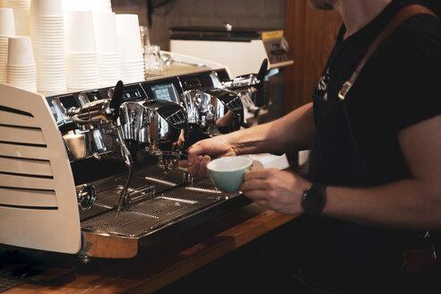 Close-up of barista preparing a coffee in coffee shop - OCMF00421