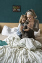 Mother taking temperature of sick daughter lying in bed - PSIF00255