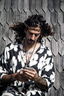Curly haired man with jamaican shirt using mobile phone. - OCMF00434