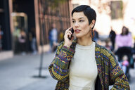 Smiling fashionable young woman on cell phone in the city - JSMF00968