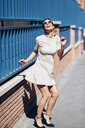 Happy fashionable young woman wearing dress and sunglasses - JSMF00974