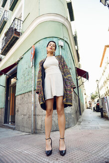 Spain, Madrid, Madrid. Young woman, with very short haircut, wearing dress and jacket, standing in urban background. Lifestyle concept. - JSMF00980