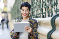 Smiling fashionable young woman using tablet outdoors - JSMF00986