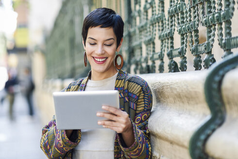 Spain, Madrid, Madrid. Young woman with very short haircut, wearing dress and jacket using digital tablet outdoors. Lifestyle concept. - JSMF00986