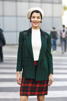 Spain, Madrid, Madrid. Modern woman, wearing green jacket, checked skirt and white beret, standing in the street. Lifestyle concept. - JSMF00992