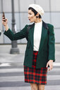 Fashionable young woman taking a selfie on zebra crosssing - JSMF00995