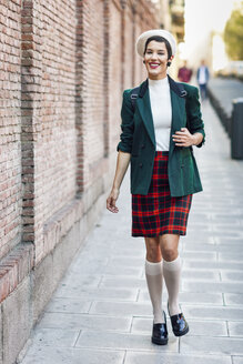 Spain, Madrid, Madrid. Modern woman, wearing green jacket, checked skirt and white beret, standing in the street. Lifestyle concept. - JSMF01001