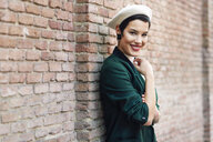 Portrait of smiling fashionable young woman at a brick wall - JSMF01004