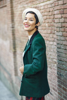 Portrait of smiling fashionable young woman at a brick wall - JSMF01010