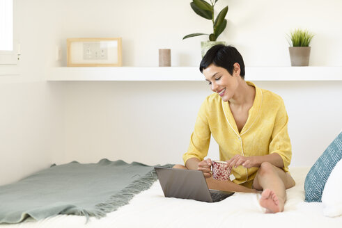 Spain, Madrid, Madrid. Woman with very short hair wearing summer pajamas on her bed using laptop computer. Lifestyle concept. - JSMF01019