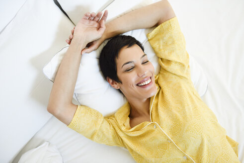 Smiling young woman lying in bed - JSMF01034