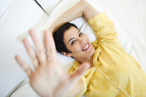Portrait of smiling young woman lying in bed - JSMF01037