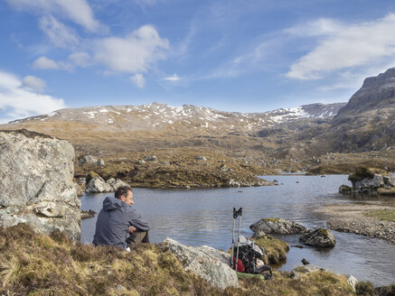 Großbritannien, Schottland, Northwest Highlands, rastender Wanderer am Ben More Assynt - HUSF00037
