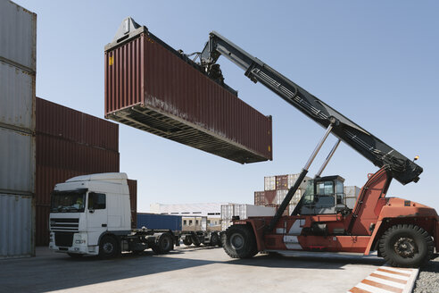 Spain, Aragon, Zaragoza, crane lifting cargo container on truck in logistics company - AHSF00167