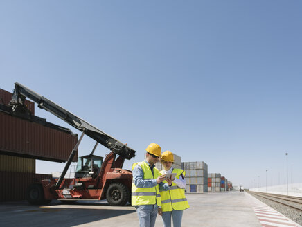 Workers using tablet in front of crane with cargo container on industrial site - AHSF00173