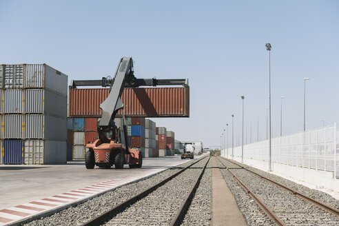 Crane lifting cargo container near railway tracks on industrial site - AHSF00176