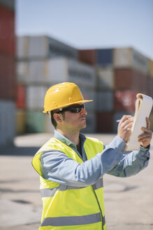 Worker with a notepad near cargo containers on industrial site - AHSF00182