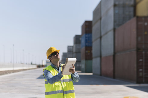 Worker with a notepad near cargo containers on industrial site - AHSF00185