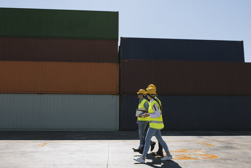 Spain, Aragon, Zaragoza, workers walking together near stack of cargo containers - AHSF00194