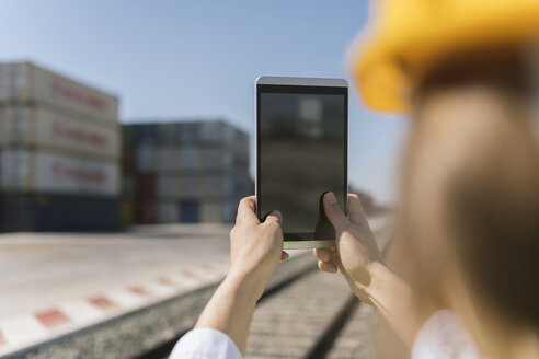 Close-up of female worker holding tablet on railway near to cargo containers on industrial site - AHSF00200