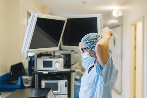 Female doctor tying surgical mask, preparing for surgery - JCMF00048