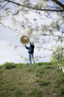Teenage boy helping with a photo shooting, holding reflector - KMKF00872