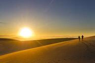 Hispanic couple walking on sand dune at sunset - BLEF00181