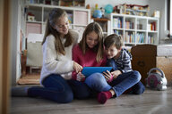 Siblings playing at home with their digital tablets, sitting on ground - RBF07018