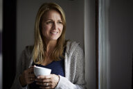 Smiling woman drinking coffee, looking out of window - RBF07030