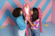 Two young women at an indoor theme park kissing a unicorn figure - AFVF02807