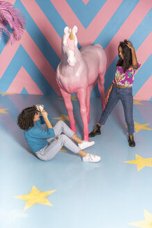 Young woman taking a picture of her friend at an indoor theme park with a unicorn figure - AFVF02810