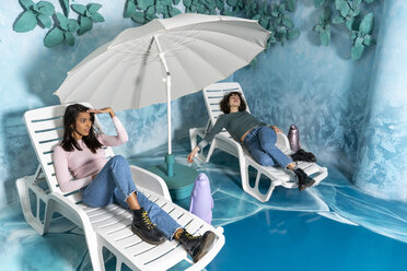 Two young women at an indoor theme park lying on sun loungers at an artificial sea - AFVF02816