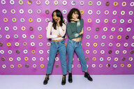Two young women posing at an indoor theme park with donuts at the wall - AFVF02819