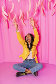Young woman screaming at an indoor theme park with dangling pink bananas - AFVF02822