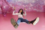 Portrait of happy young woman on a swing at an indoor theme park - AFVF02825