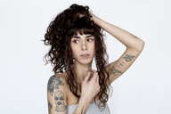 Portrait of tattooed young woman with hand in hair - FLLF00124