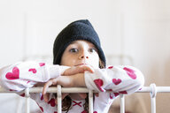 Portrait of starring little girl in bed wearing cap and pyjama - ERRF01191