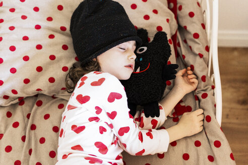 Little girl wearing cap sleeping in bed with her soft toy - ERRF01194