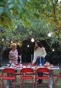 Women friends setting table for dinner garden party - CAIF23217