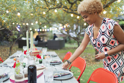 Woman setting table for dinner garden party - CAIF23220