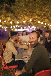 Portrait happy man enjoying dinner garden party - CAIF23226