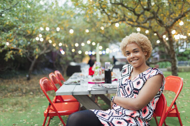 Portrait happy woman hosting dinner garden party - CAIF23232