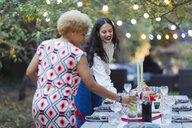 Women friends setting table for dinner garden party - CAIF23235