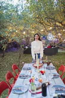 Portrait confident woman hosting dinner garden party - CAIF23256