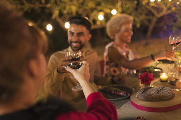 Friends toasting wine glasses at dinner garden party - CAIF23259