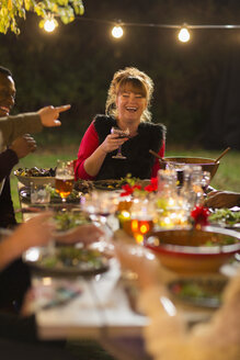 Happy woman laughing, enjoying dinner garden party with friends - CAIF23262